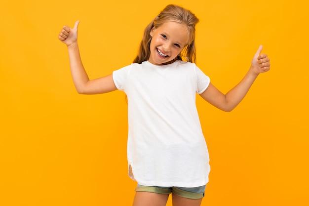 Niña rubia sonriente en una camiseta blanca con una maqueta Foto Premium