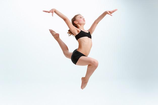 La niña saltando como bailarina de ballet moderno Foto gratis