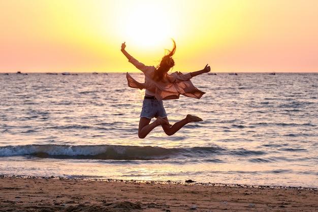 Niña saltando en la playa al atardecer de verano. Foto Premium