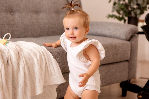 Niña sana en una habitación junto a un sofá gris está aprendiendo a caminar Foto Premium
