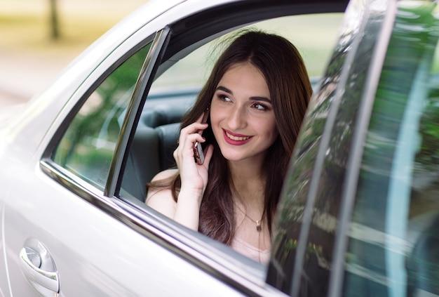 Una niña está sentada en el asiento trasero de un automóvil y está hablando por teléfono. Foto Premium