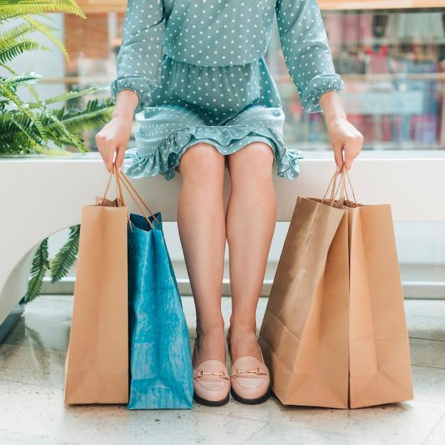 Niña sentada con bolsas de la compra Foto gratis