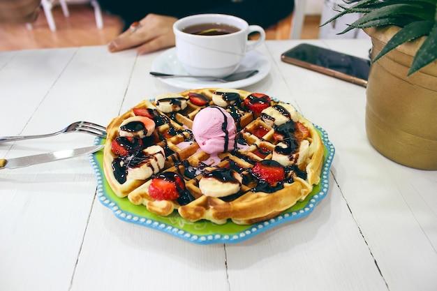 Niña sentada caffe comiendo desayuno waffle con salsa de chocolate, rodajas de plátano y fresas en un plato de cerámica verde y fotografió su desayuno Foto gratis