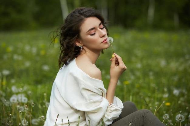 Niña sentada en un campo en la hierba de primavera con flores de diente de león Foto Premium