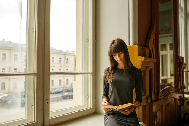 Niña sentada cerca de la ventana leyendo un libro Foto Premium