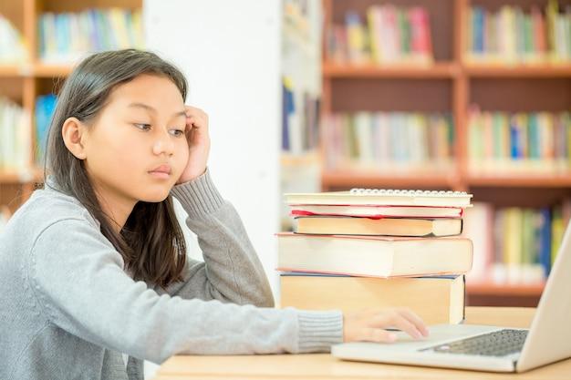 Una niña está sentada para leer un libro en la biblioteca Foto gratis