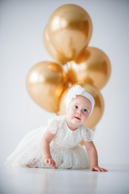 Niña sentada con un montón de globos dorados Foto Premium