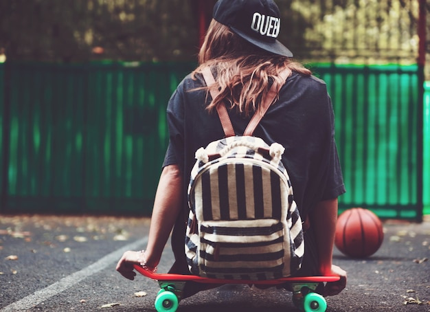 Niña sentada en plástico naranja penny shortboard sobre asfalto en la tapa Foto gratis