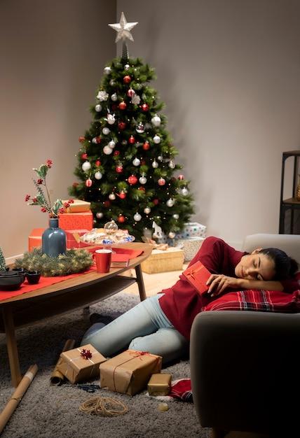 Niña sentada en un puente rojo con un fondo de navidad Foto gratis