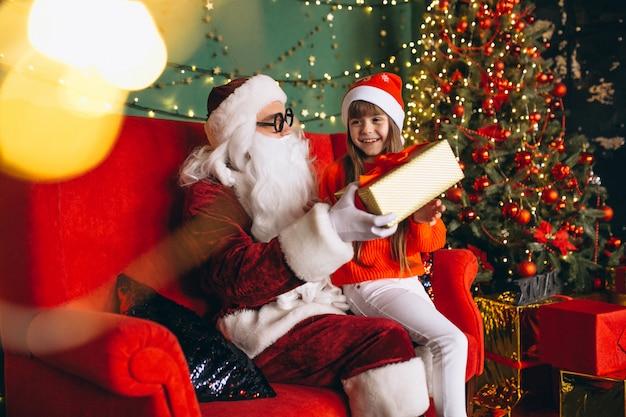 Niña sentada con santa y regalos en navidad Foto gratis