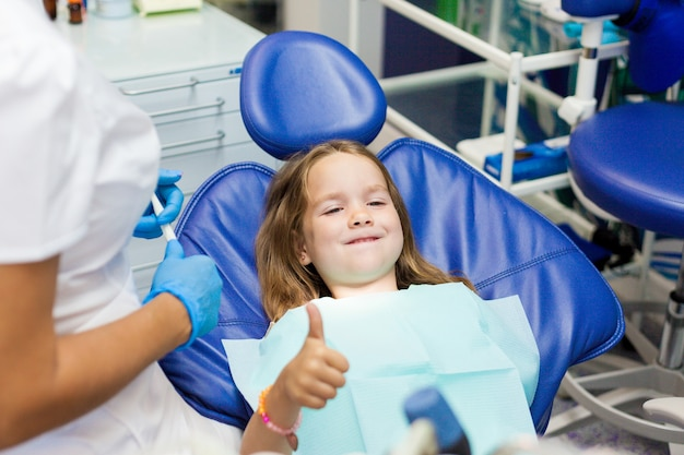 Niña sentada en la silla del dentista. Foto Premium