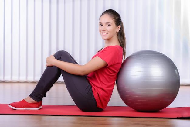 Una niña sentada sobre una estera junto a su pelota de fitness. Foto Premium