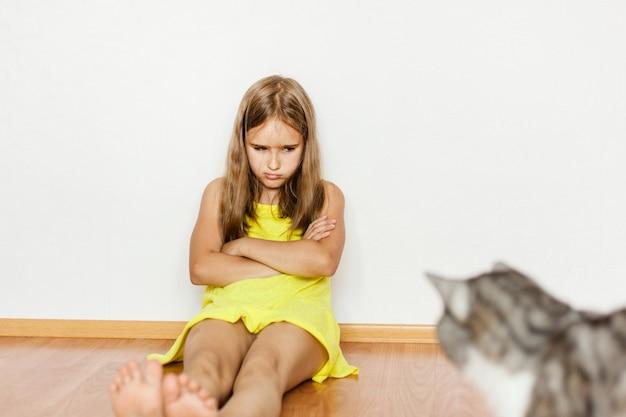 Niña sentada en el suelo, molesta, ofendida por el gato, mascota, rasguñada, mano, pies, vestido amarillo, bebé, familia, cuidado de mascotas Foto Premium