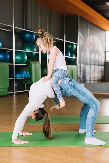 Niña sentada en el vientre de su madre mientras hace ejercicio en el gimnasio Foto gratis