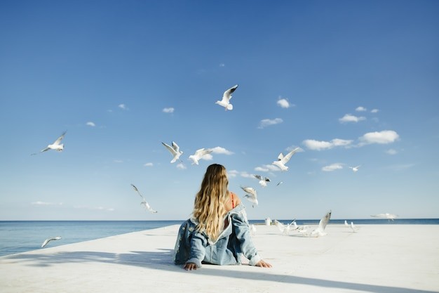 Una niña se sienta en la litera y observa a las gaviotas Foto gratis