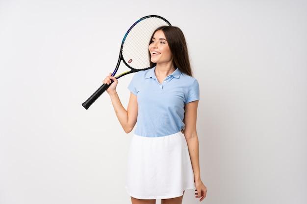 Niña sobre pared blanca aislada jugando tenis y mirando hacia arriba Foto Premium