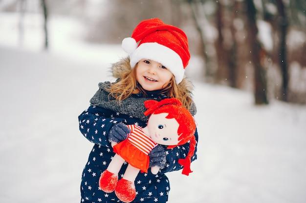 Niña en un sombrero azul jugando en un bosque de invierno Foto gratis