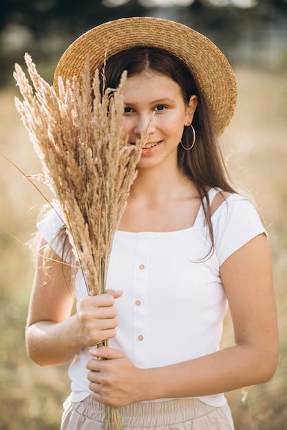Niña con sombrero en un campo de trigo Foto gratis