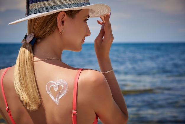 Una niña en un sombrero con protector solar en forma de un corazón en la espalda en la playa. Foto Premium