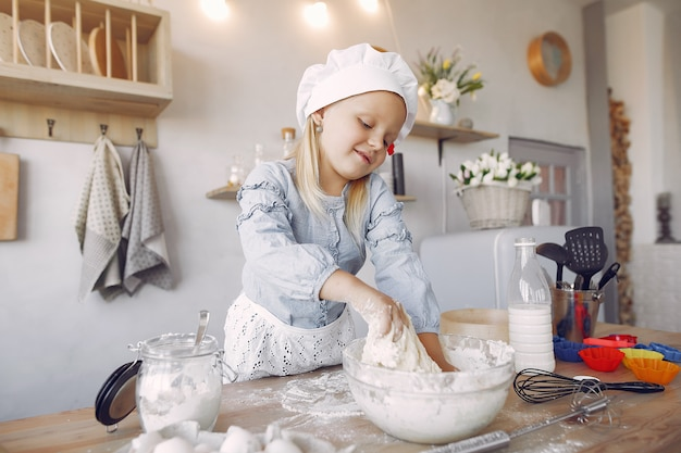 Niña en un sombrero de shef blanco cocinar la masa para galletas Foto gratis