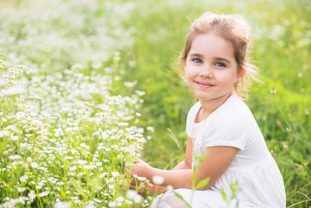 Niña sonriente agachándose cerca de la flor silvestre en el campo Foto gratis