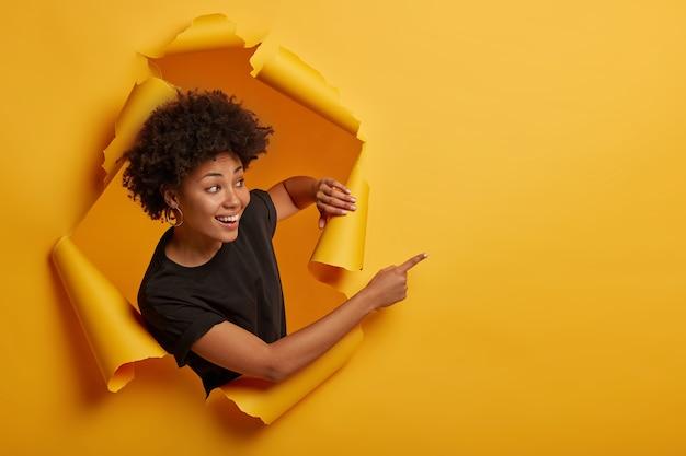 La niña sonriente de aspecto alegre y amigable señala a un lado con expresión feliz, sonrisa con dientes, encantada de mostrar un anuncio impresionante Foto gratis