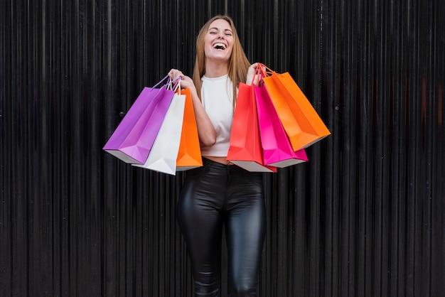 Niña sonriente con bolsas de compras Foto gratis