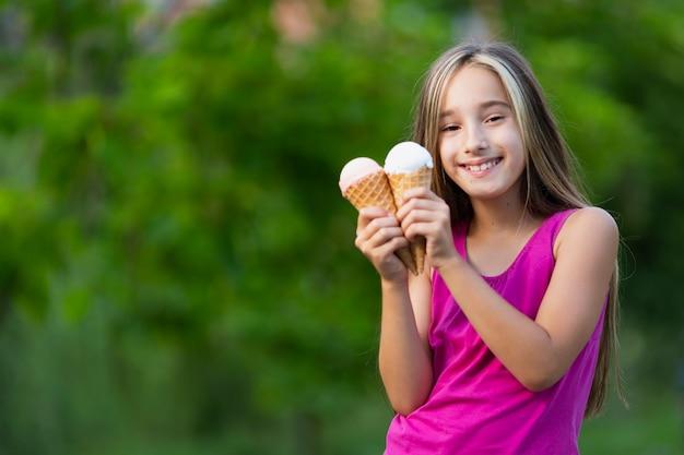 Niña sonriente con conos de helado Foto gratis