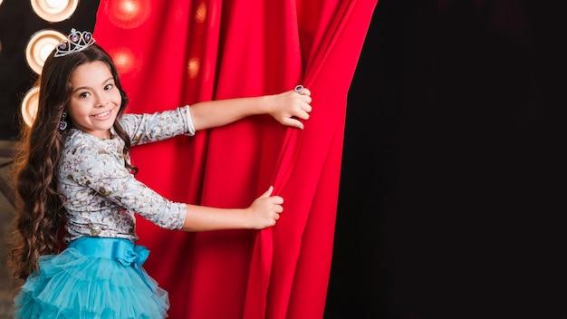 Niña sonriente con corona abriendo la cortina roja Foto gratis
