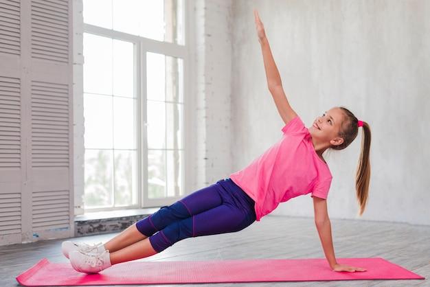 Niña sonriente haciendo ejercicios de estiramiento en el gimnasio Foto gratis