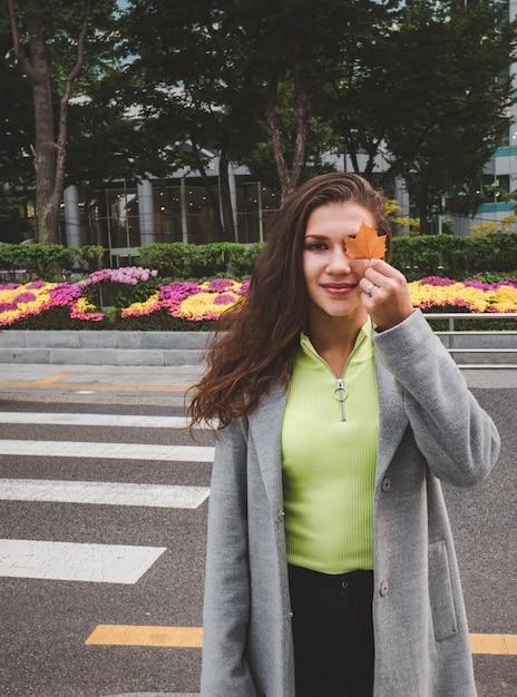 Niña sonriente con hoja de otoño en seúl Foto Premium