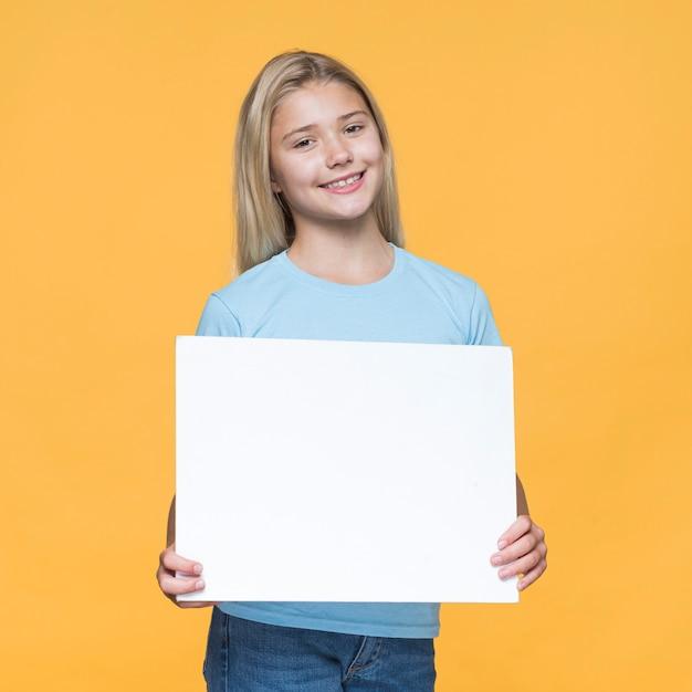 Niña sonriente con hoja de papel en blanco Foto gratis
