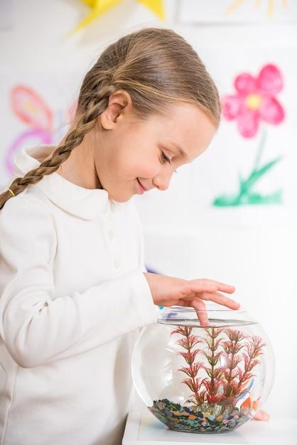 Niña sonriente en jersey blanco jugando con peces dorados. Foto Premium