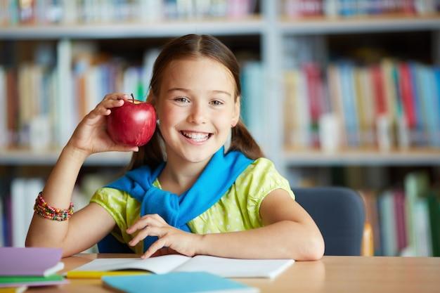 Niña sonriente con una manzana Foto gratis