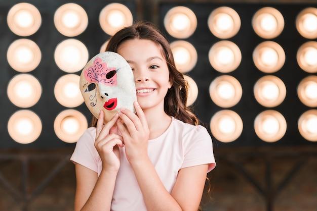 Niña sonriente con máscara veneciana en sus manos de pie delante de la luz de la etapa Foto gratis