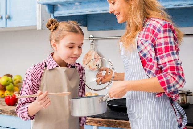 Niña sonriente oliendo la comida preparada por su madre. Foto gratis
