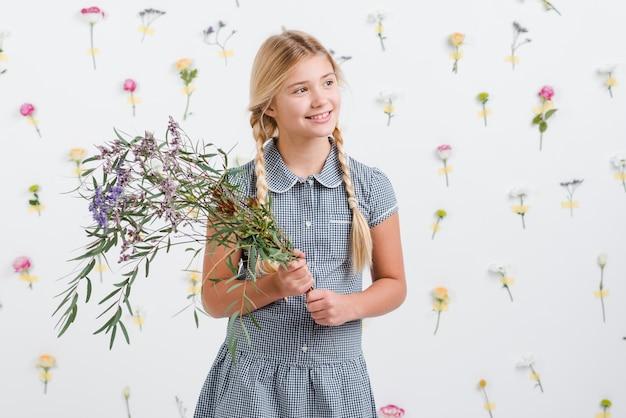 Niña sonriente con ramo de flores Foto gratis