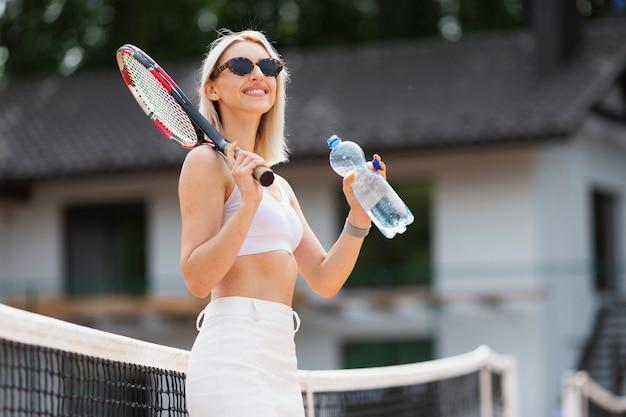 Niña sonriente con raqueta de tenis y agua Foto gratis