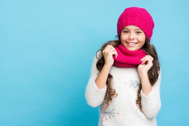Niña sonriente con sombrero y bufanda Foto gratis