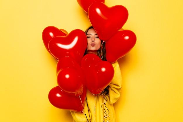 Niña sonriente en suéter amarillo dando un beso, mirando fuera de manojo de globos rojos. Foto gratis