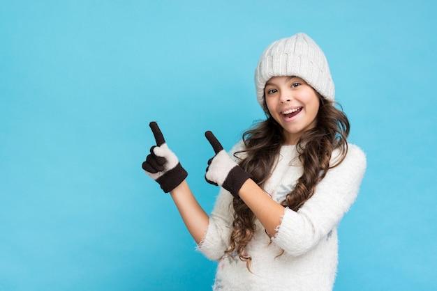 Niña sonriente vistiendo ropa de invierno señalando Foto gratis