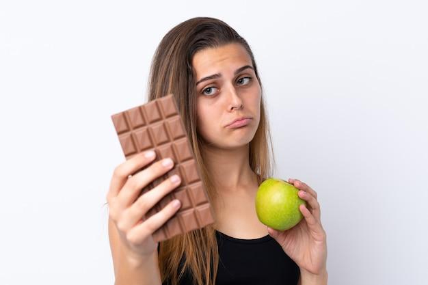 Niña sosteniendo chocolate y una manzana Foto Premium