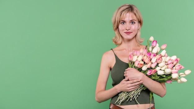 Niña sosteniendo flores y mirando al fotógrafo Foto gratis