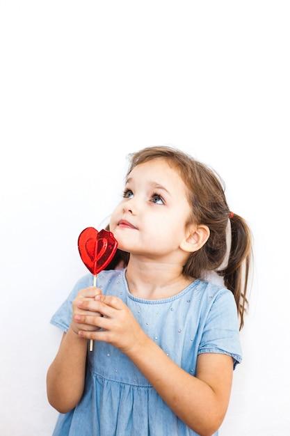 Niña sosteniendo una piruleta en forma de corazón, amantes, día de san valentín, familia y corazón Foto Premium