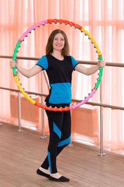 La niña sostiene un aro deportivo en sus manos. Foto Premium
