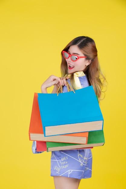 La niña sostiene una bolsa de compras de moda y tiene una tarjeta inteligente sobre un fondo amarillo. Foto gratis