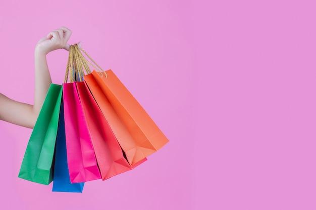 La niña sostiene un bolso de compras de moda y belleza. Foto gratis