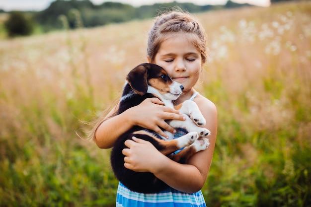 La niña sostiene un perrito en sus brazos Foto gratis