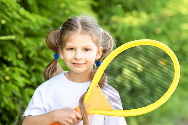 Una niña sostiene una raqueta de tenis para niños. Foto Premium