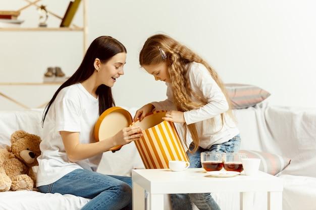 Niña y su atractiva madre joven sentada en el sofá con regalo y pasar tiempo juntos en casa. generación de mujeres. día internacional de la mujer. feliz día de la madre. Foto gratis
